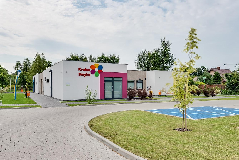 Biały budynek przedszkola z różowym frontem